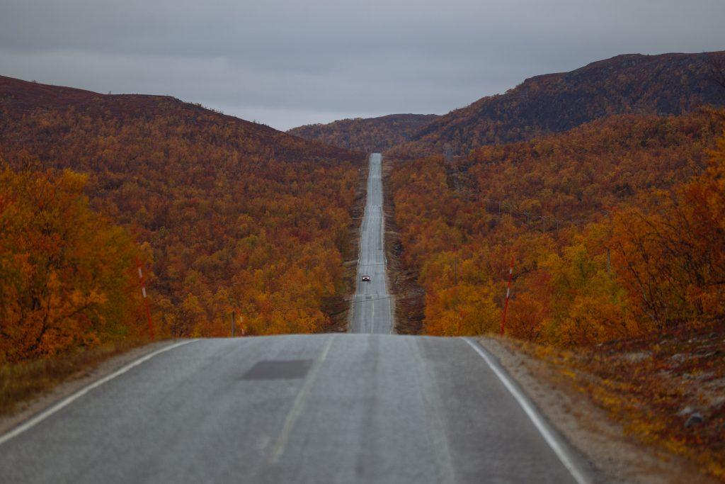 Syksyinen maantie keskellä Lapin erämaata, ruskan värittämä luonto ympärillä, on vaikuttava näky.